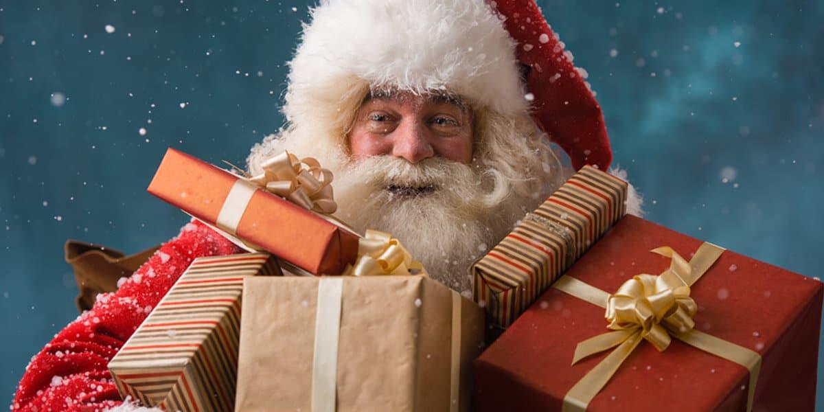 Weihnachtsmann mit vielen Geschenken und Schneeflocken