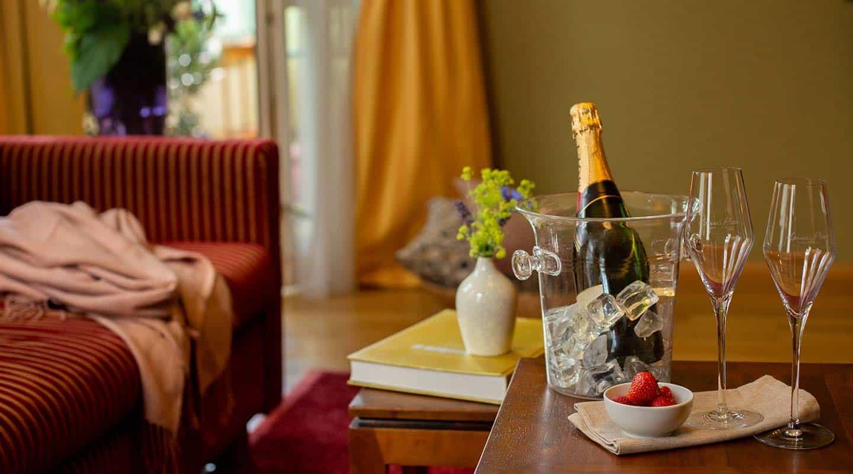Champagner, Stielgläser und Erdbeeren auf dem Tisch in der Grand Suite im Louisa's Place Berlin