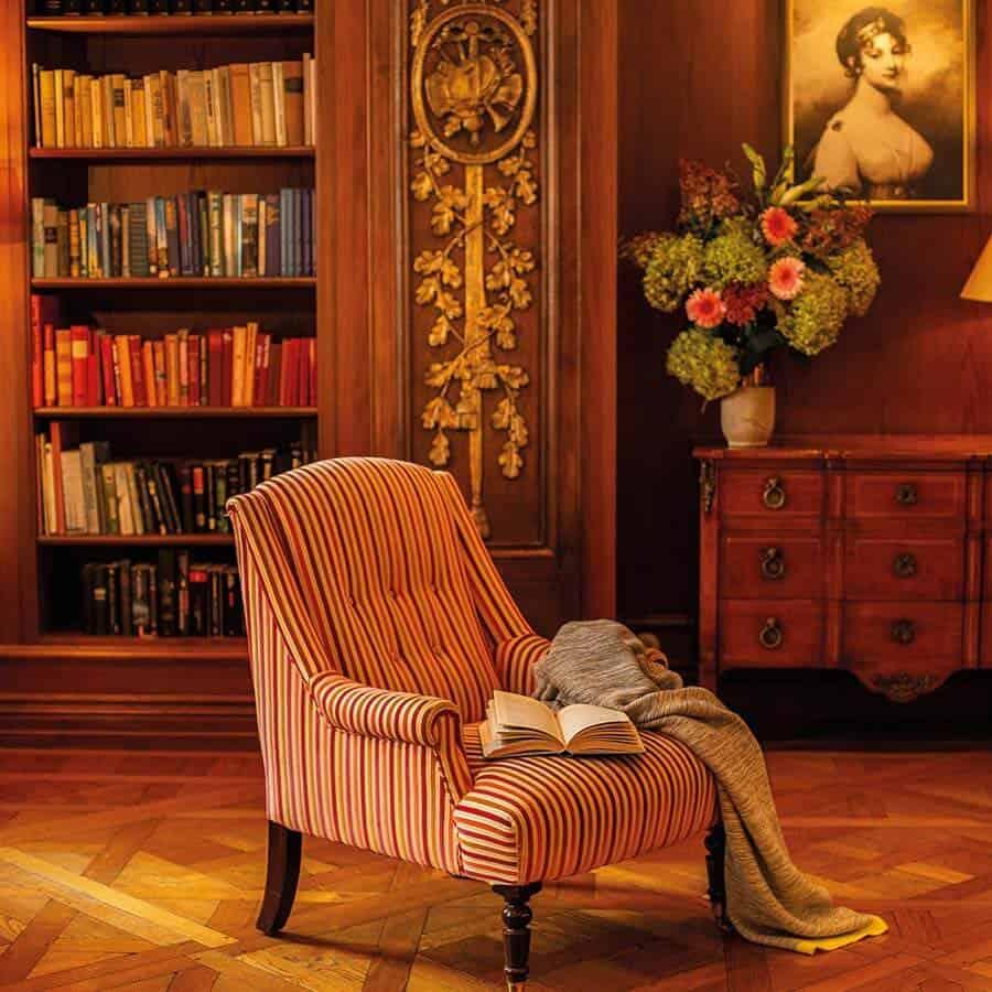 Gestreifter Sessel und Bücherregal in fürstlich eingerichteter Bibliothek des Luisa's Place Hotel Berlin
