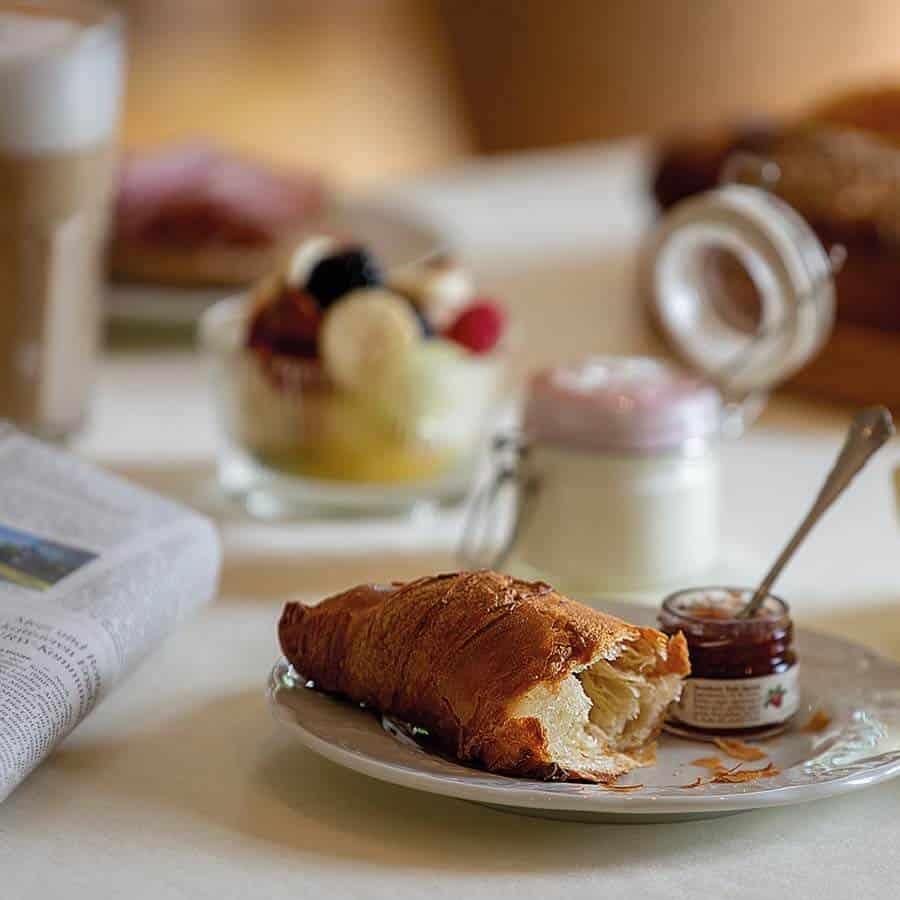Auszug der Frühstücksauswahl im Louisa's Place am Kudamm, Croissant mit Marmelade und Obstsalat mit Joghurt