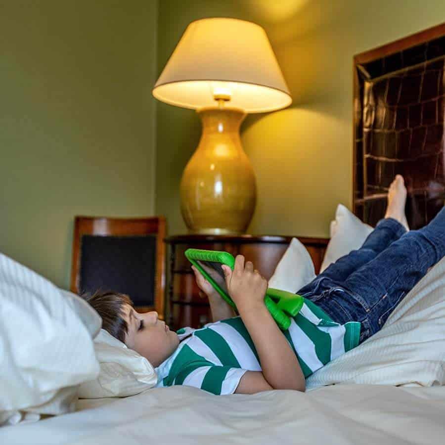 Junge liegt mit Tablet im gemütlichen Bett des Familienzimmers im Louisa's Place Hotel Kudamm Berlin
