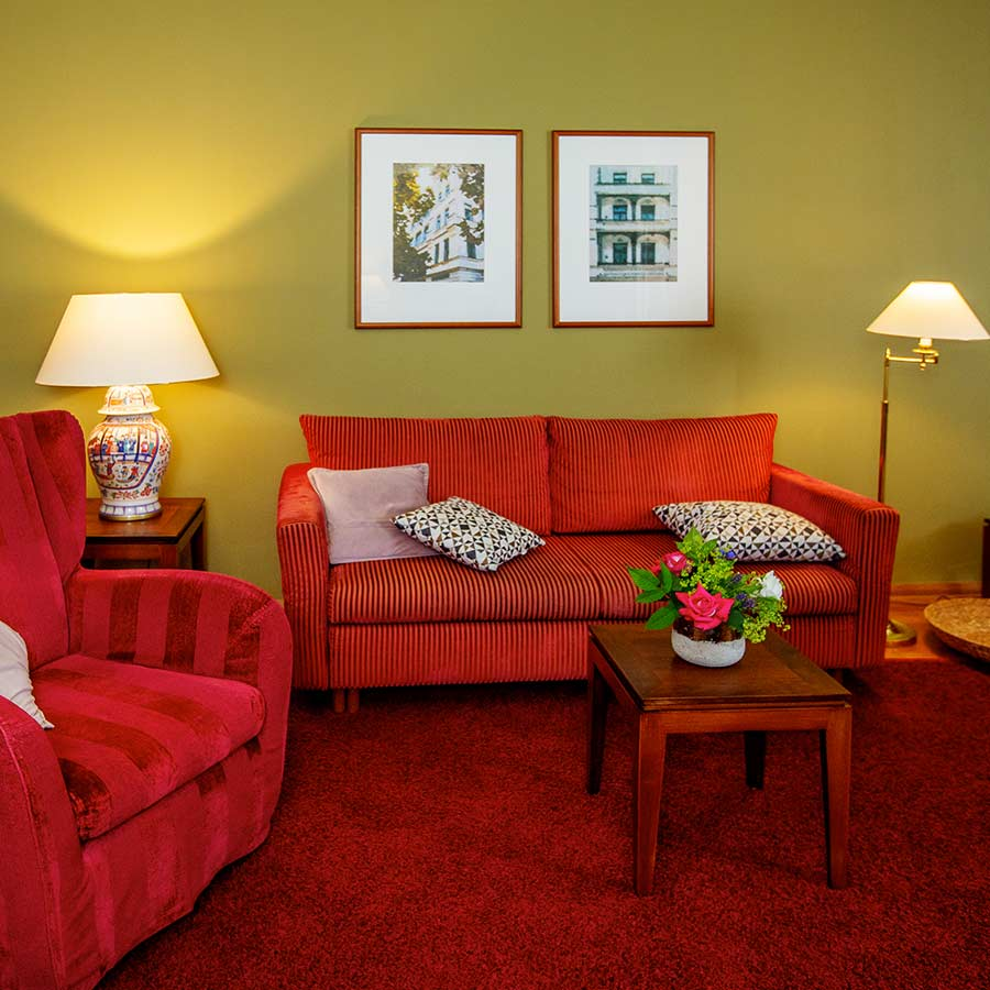 Komfortables Sofa und Beistelltisch mit Blumenstrauß im Deluxe Zimmer des Louisa's Place Hotels