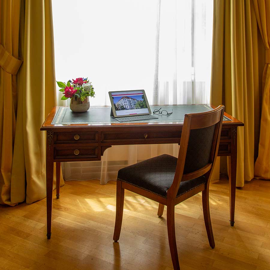 Schreibtisch mit Stuhl, Arbeitsutensilien und Blumen im Louisa's Place Hotel
