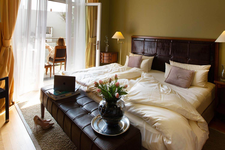 Charmantes Superior Doppelzimmer mit Tulpen, High Heels und Frau die auf dem Balkon sitzt im Louisa's Place Hotel am Kudamm