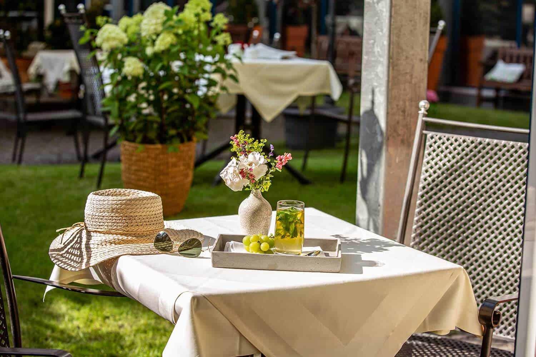 Sommerlich gedeckter Tisch mit Blumen und Getränk im Garten von Louisa's Place Hotel am Kudamm Berlin