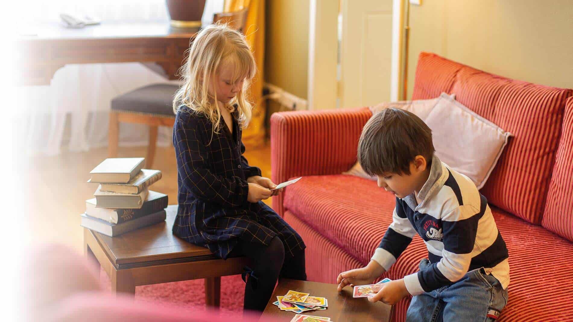Mädchen und Junge spielen gemeinsam Karten im Wohnbereich des Familienzimmers im Louisa's Place Hotel