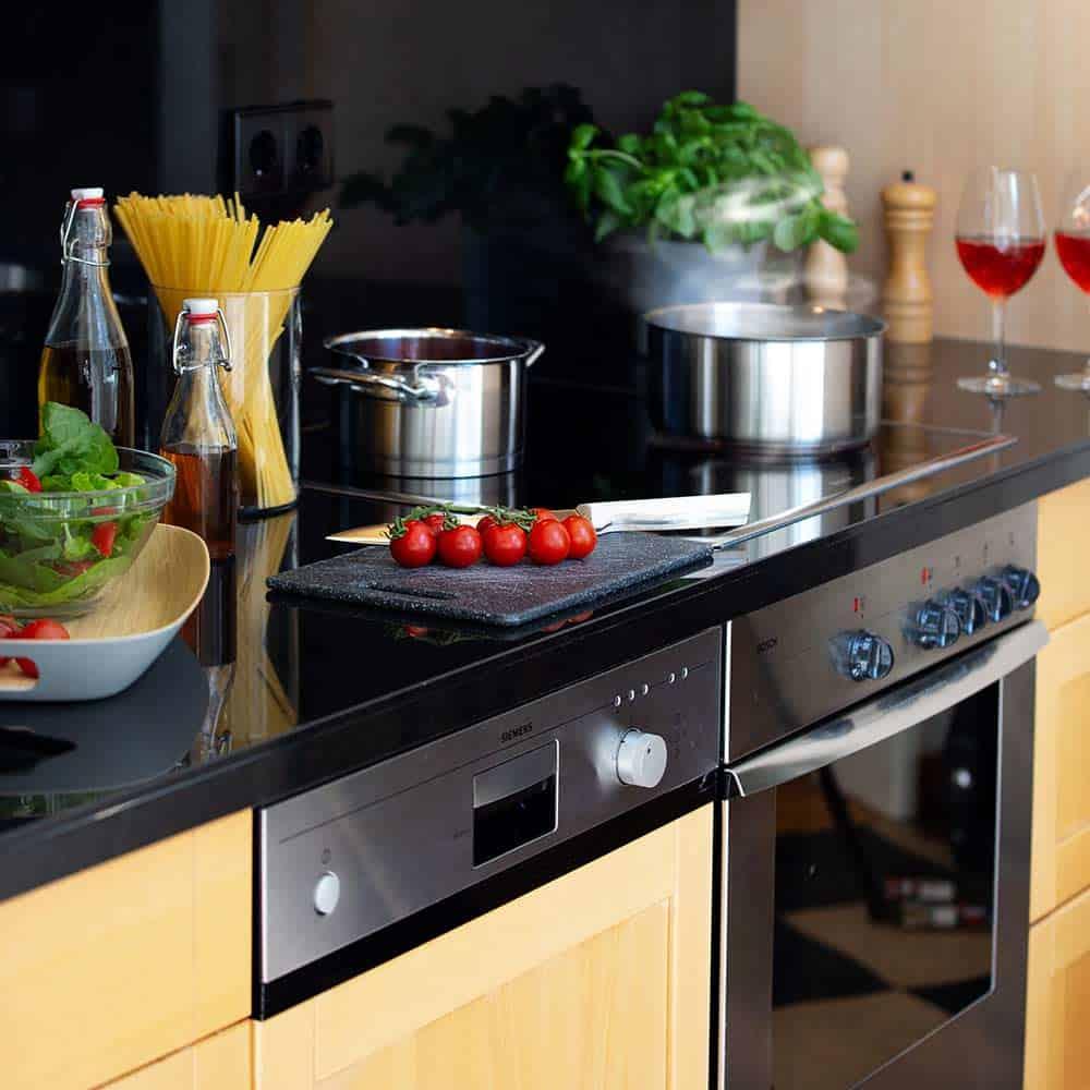 Ansicht der Küchenzeile im Premium Zimmer mit Spülmaschine und Herd, Kochtöpfen und frischen Esswaren