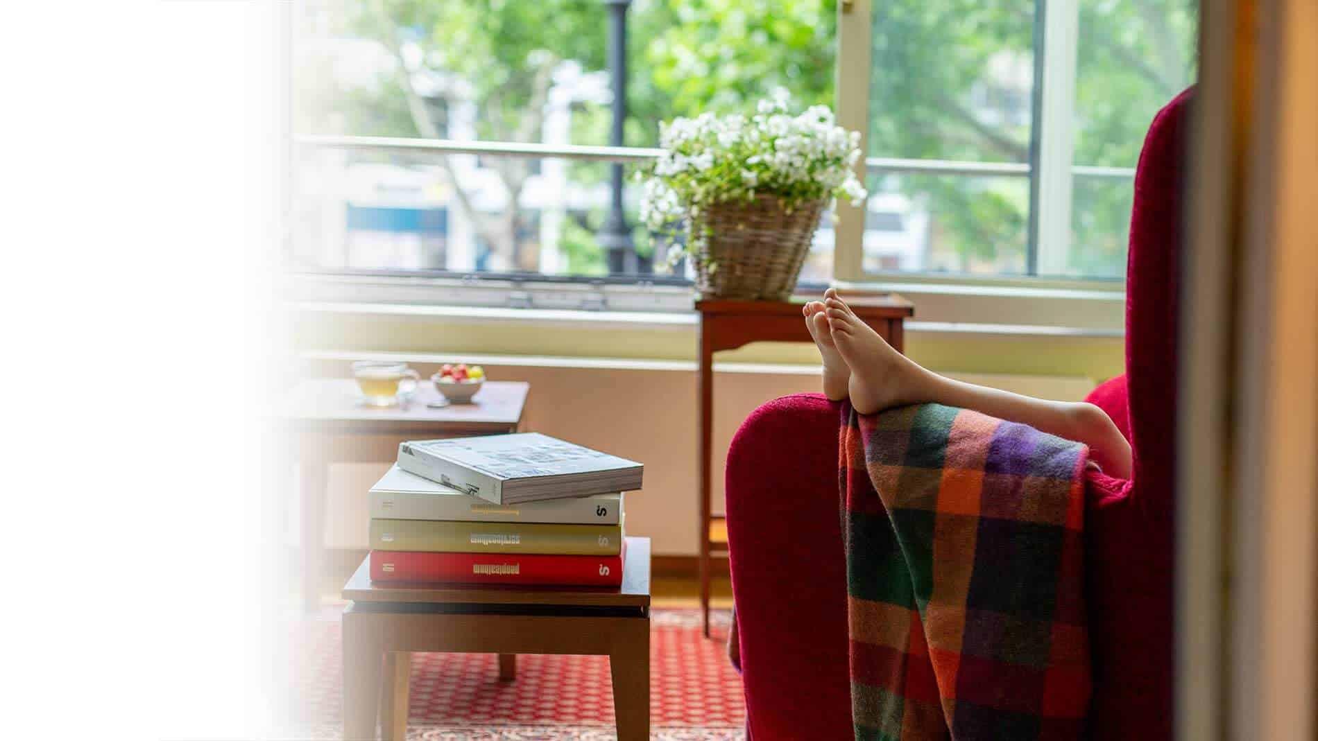 Foto aus dem Familienzimmer des Louisa's Place Hotel, Kinderfüße ragen über einen roten Sessel mit karierter Decke hervor, im Hintergrund ein Tisch mit Büchern und das Fenster