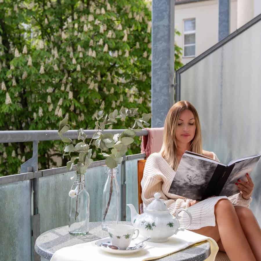 Frau sitzt auf dem Balkon des Premium Zimmers und liest ein Buch, vor ihr der eingedeckte Kaffeetisch mit Dekoration