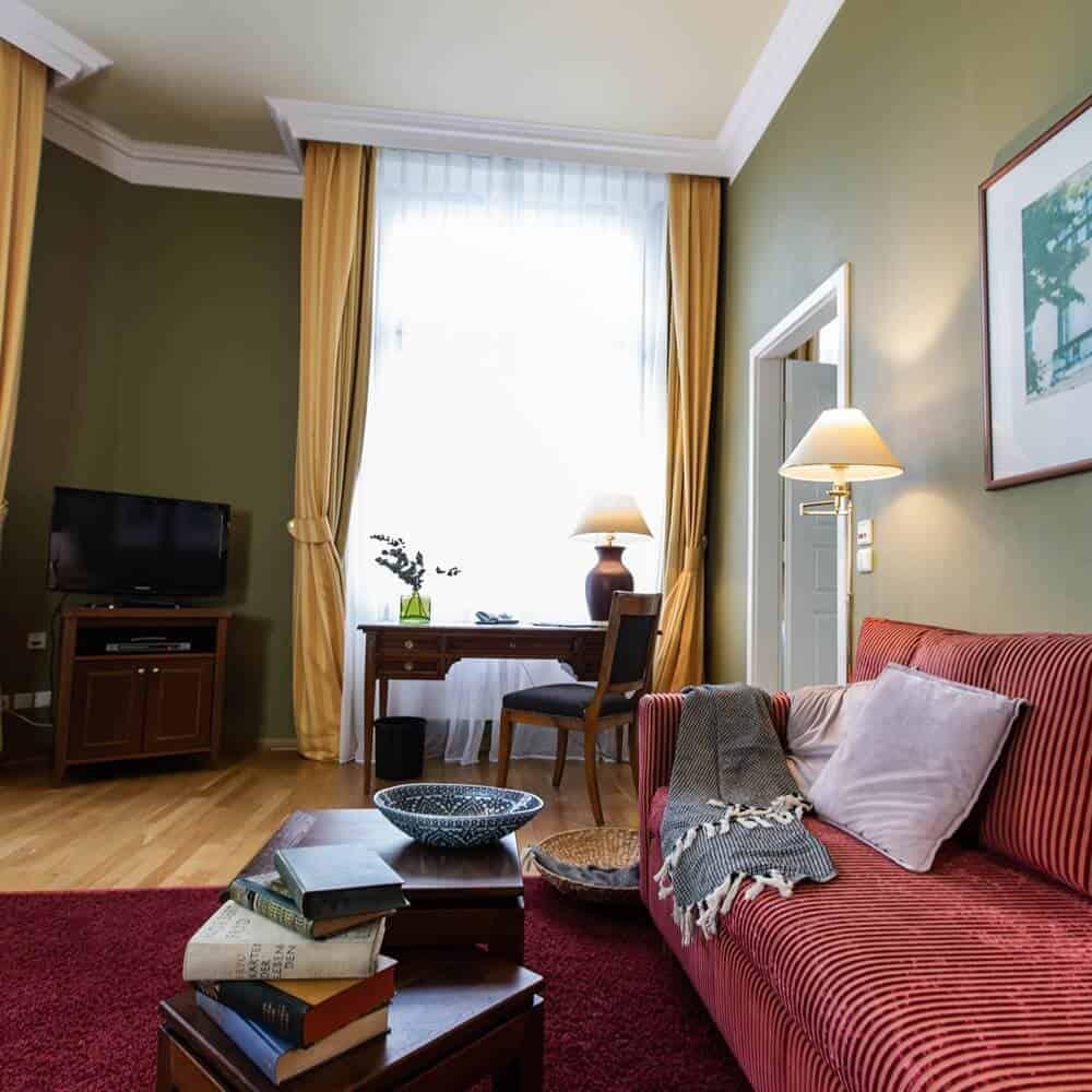 Gemütliches rotes Sofa mit Kissen und Decke und Flatscreen in der Louisa's Place Grand Suite