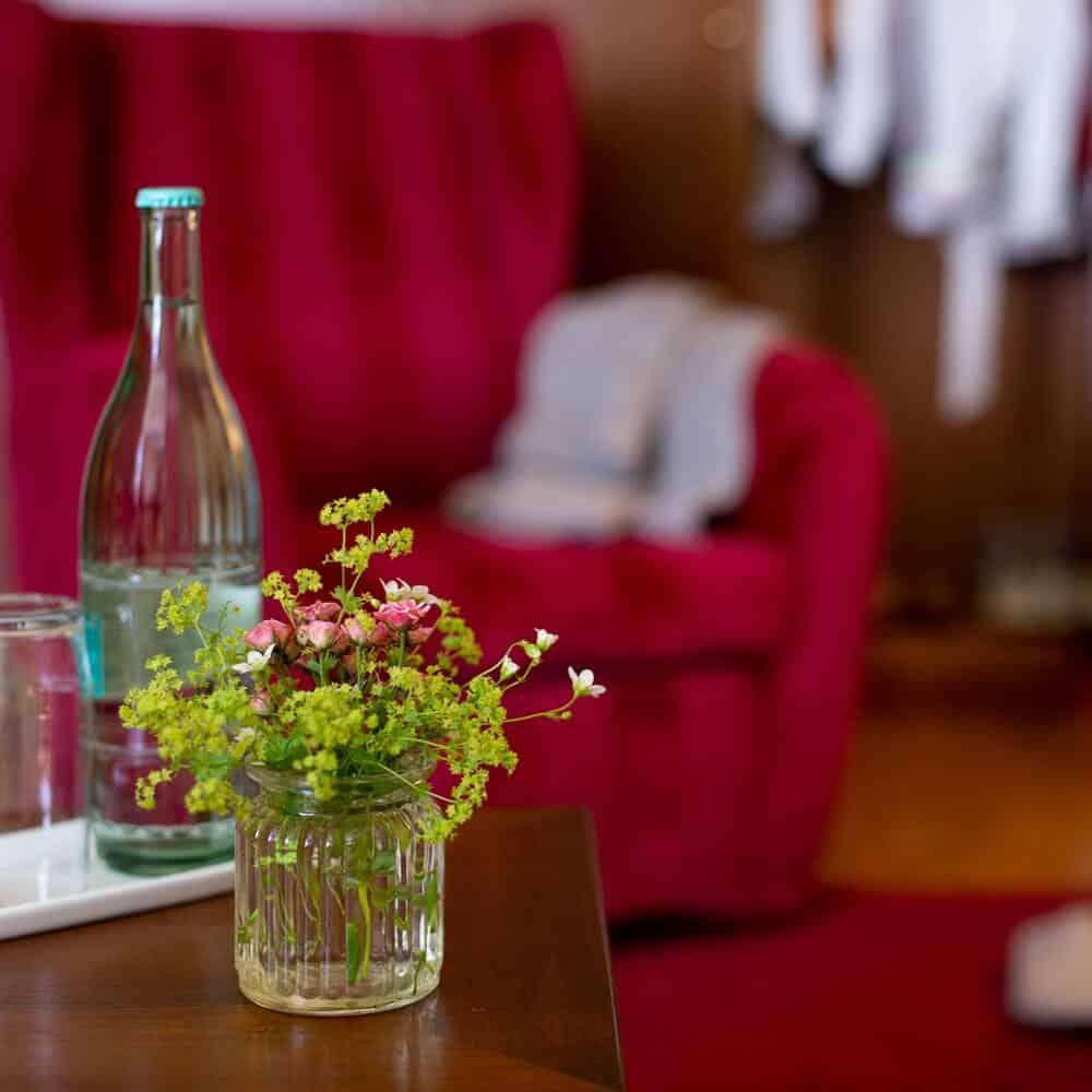 Wasserflasche und kleine Vase mit Blumen auf einem hölzernen Wohnzimmertisch in der Grand Suite des Louisa's Place Hotel
