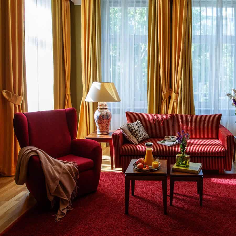 Sitzecke mit Sessel, Sofa und hölzernen Beistelltischen in Luisa's Suite im Boutiquehotel am Kudamm Berlin