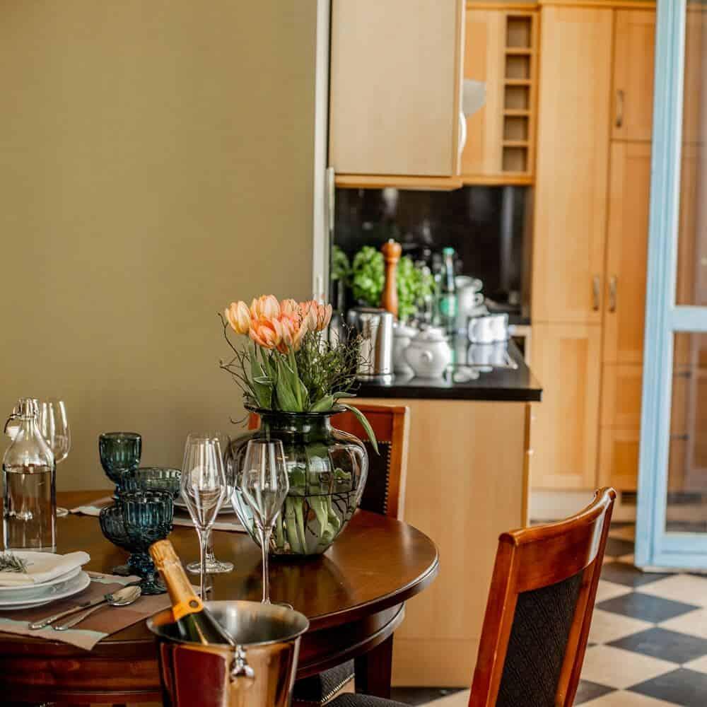 Großzügige Küche mit geschmackvoll gedecktem Tisch und gläserner Tulpenvase in Louisa's Suite