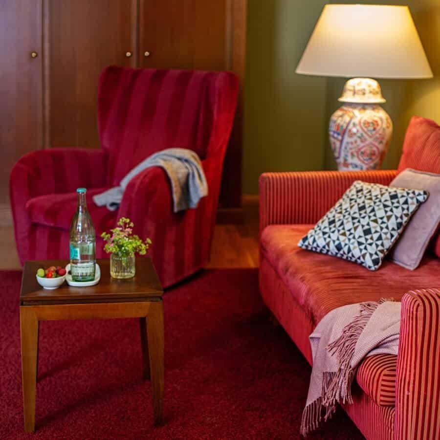 Wohnbereich des Premium Zimmers mit komfortablen Sitzgelegenheiten und Sofatisch mit Wasser und Obst