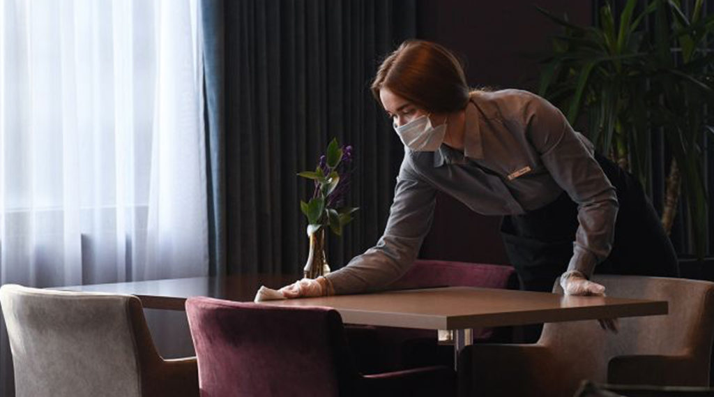 Mitarbeiterin mit Mundschutz und Handschuhen reinigt einen Tisch im Louisa's Place in Berlin